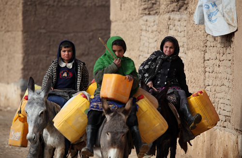 In this photo, Afghan girls in the northern Afghan province of Balkh head out to fetch drinking water from a nearby river. Photo: Fardin Waezi / UNAMA